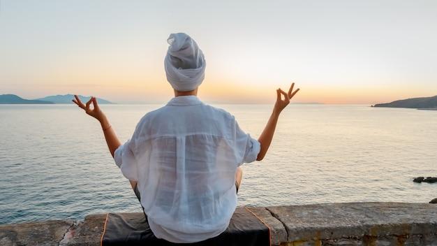 Блондинка делает дыхательные упражнения пранаямы на закате на море. .