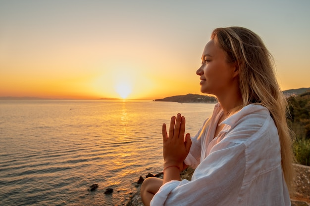 Blonde woman doing breathing pranayama exercise on sunset on the sea.