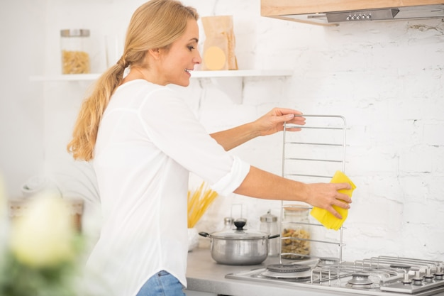 Blonde woman doing cleaning in the kitchen