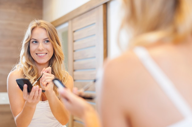 Blonde woman doing makeup in front of mirror
