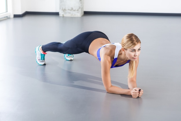 Blonde woman doing push up or plank. studio shot, isolated on gray background