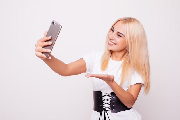 Blonde woman doing selfie on isolated
