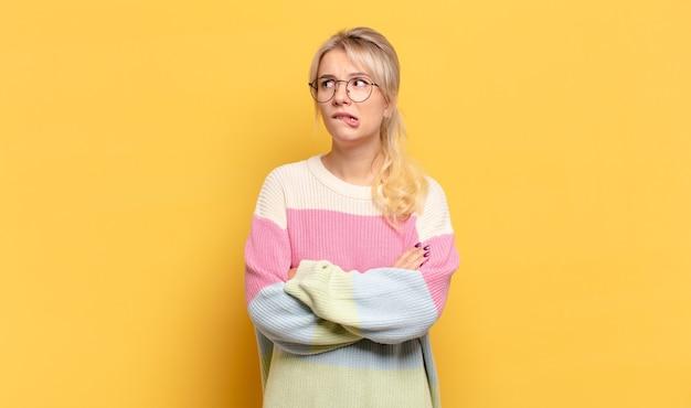 Блондинка сомневается или думает, кусает губу и чувствует себя неуверенно и нервно, пытаясь скопировать пространство сбоку