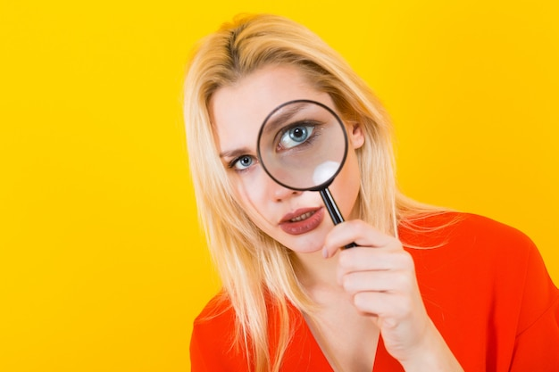 Blonde woman in dress with magnifying glass
