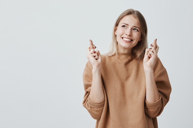 Blonde woman dressed in beige sweater, crosses fingers and has great hope