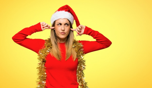 Blonde woman dressed up for christmas holidays covering ears with hands on yellow background