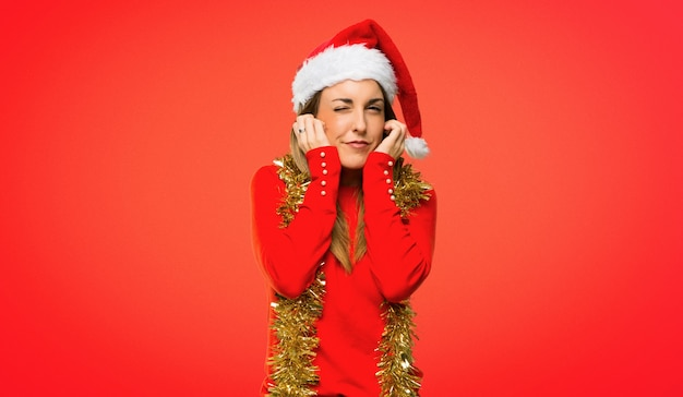 Blonde woman dressed up for christmas holidays covering ears with hands