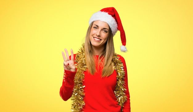 Blonde woman dressed up for christmas holidays happy and counting three with fingers