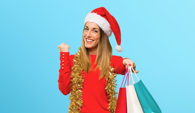 Blonde woman dressed up for christmas holidays holding a lot of shopping bags on blue background