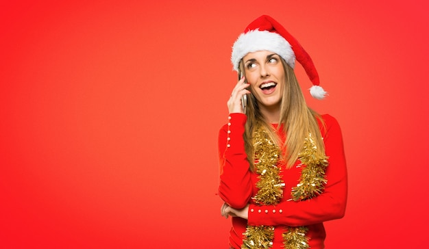 Blonde woman dressed up for christmas holidays keeping a conversation with the mobile