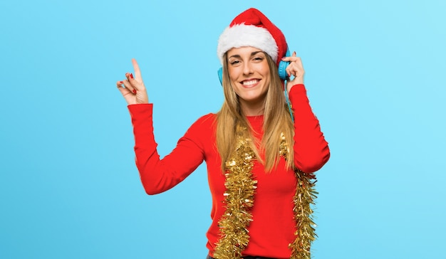 Blonde woman dressed up for christmas holidays listening to music with headphones
