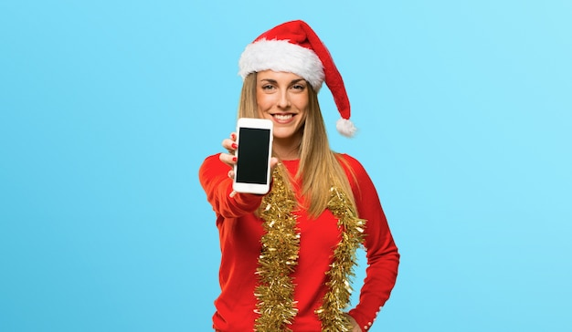 Blonde woman dressed up for christmas holidays looking at the camera and smiling