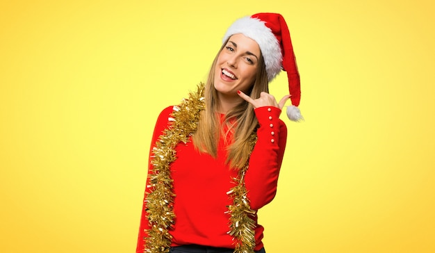 Blonde woman dressed up for christmas holidays making phone gesture
