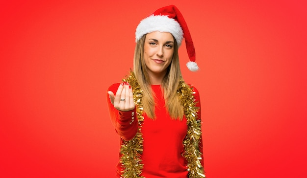Blonde woman dressed up for christmas holidays presenting and inviting to come with hand
