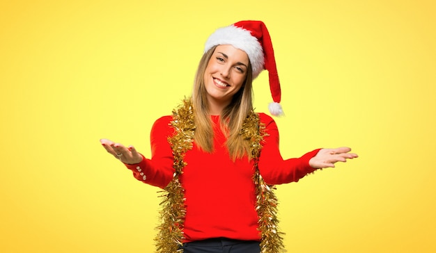 Blonde woman dressed up for christmas holidays presenting and inviting to come