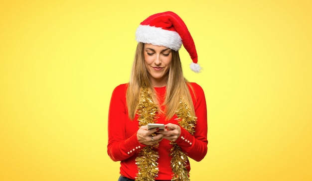 Blonde woman dressed up for christmas holidays sending a message or email with the mobile
