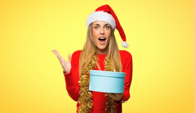 Blonde woman dressed up for christmas holidays surprised because has been given a gift