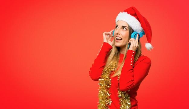 Блондинка женщина, одетая на рождественские каникулы, слушая музыку с наушниками на красном фоне