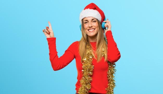 Блондинка, одетая на рождественские каникулы, слушая музыку с наушниками