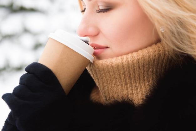 冬の公園でコーヒーを飲みながらブロンドの女性