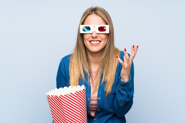 Blonde woman eating popcorns annoyed angry in furious gesture