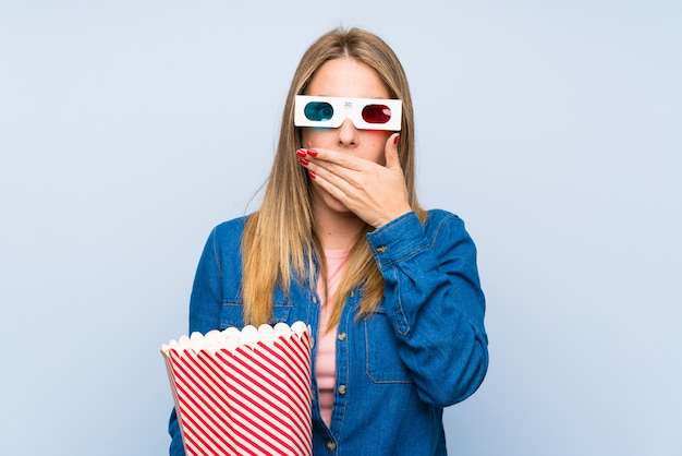 Blonde woman eating popcorns covering mouth with hands