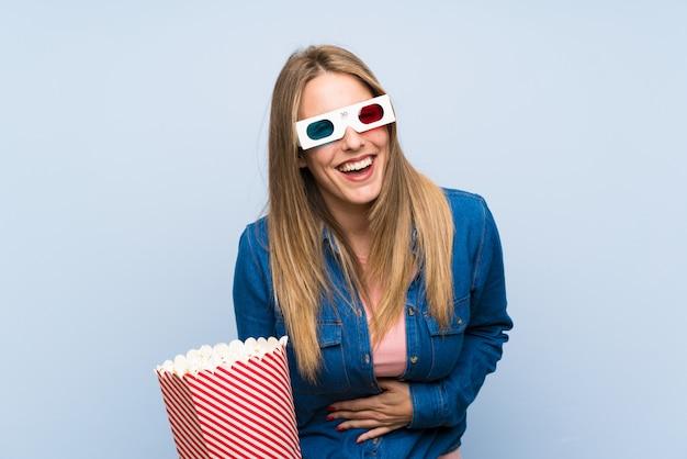 Blonde woman eating popcorns laughing