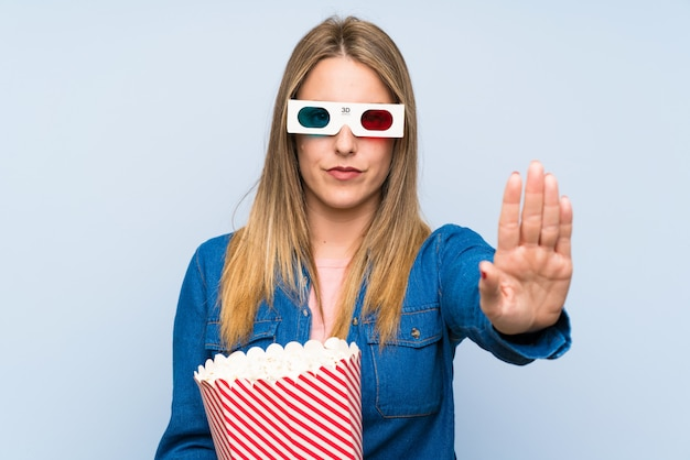 Blonde woman eating popcorns making stop gesture with her hand