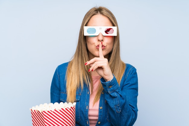 Blonde woman eating popcorns showing a sign of closing mouth and silence gesture