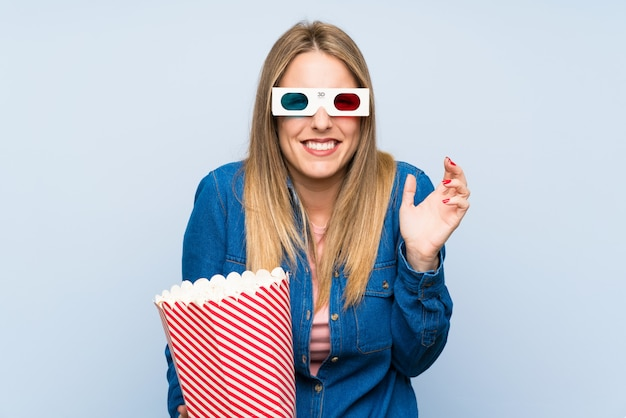 Blonde woman eating popcorns unhappy and frustrated with something. negative facial expression