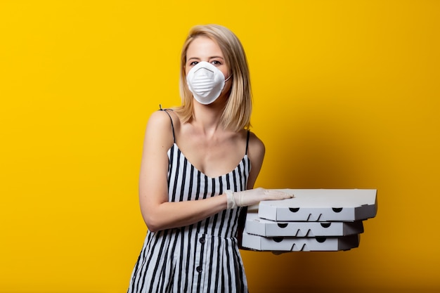 Blonde woman in face mask and gloves holds pizza boxes