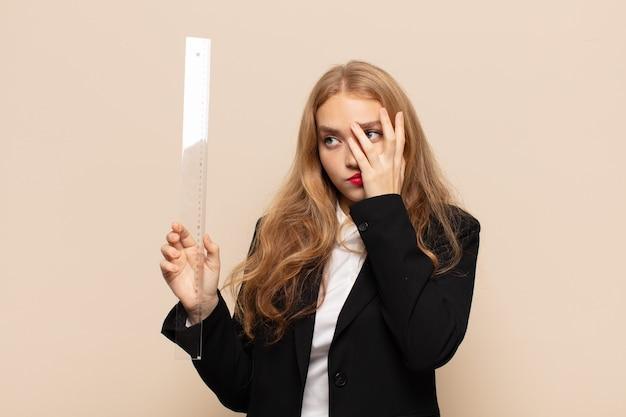 Блондинка чувствует скуку, разочарование и сонливость после утомительной, скучной и утомительной работы, держа лицо рукой