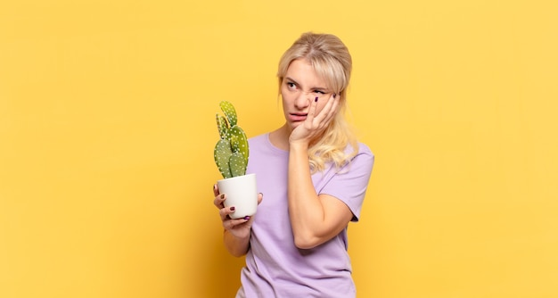 Blonde woman feeling bored, frustrated and sleepy after a tiresome, dull and tedious task, holding face with hand