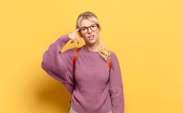Блондинка смущена и озадачена, показывая, что вы сошли с ума, сошли с ума или сошли с ума