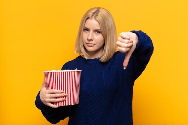 Блондинка чувствует раздражение, злость, раздражение, разочарование или недовольство, показывая большие пальцы вниз с серьезным взглядом