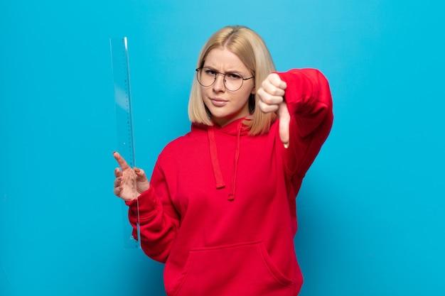 Блондинка чувствует себя сердитой, сердитой, раздраженной, разочарованной или недовольной, показывает палец вниз с серьезным взглядом