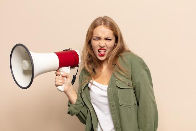 Блондинка чувствует отвращение и раздражение, высунула язык, не любит что-то противное и противное