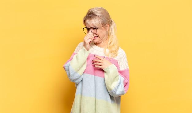 嫌な感じの金髪女性、悪臭や不快な悪臭を避けるために鼻を保持