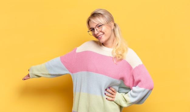 Блондинка чувствует себя счастливой и веселой, улыбается и приветствует вас, приглашая вас дружелюбным жестом