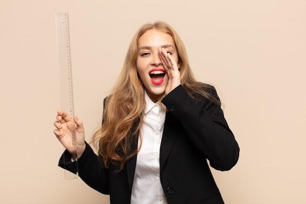 Блондинка чувствует себя счастливой, взволнованной и позитивной, громко кричит, прижав руки ко рту, выкрикивая
