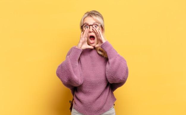 금발의 여인이 행복하고 흥분되고 긍정적 인 느낌, 입 옆에 손으로 큰 소리를 지르고 외침