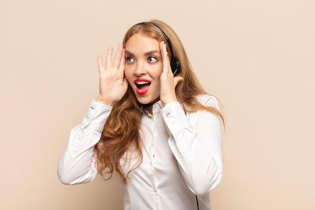 금발의 여인이 행복하고 흥분되고 놀란 느낌, 얼굴에 양손으로 측면을 찾고