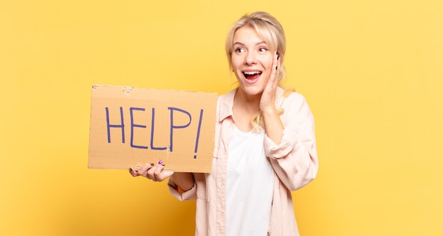 Blonde woman feeling happy, excited and surprised, looking to the side with both hands on face