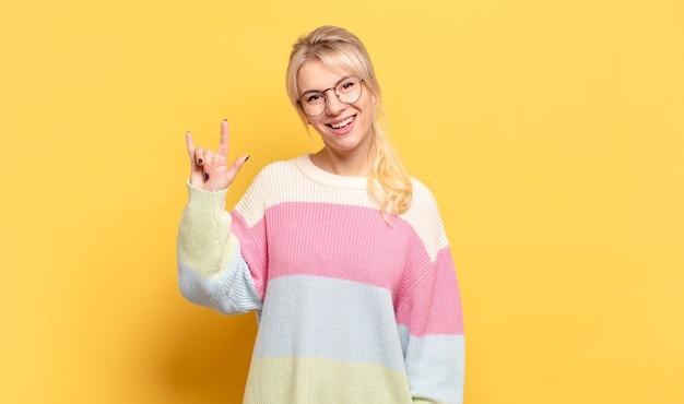 Блондинка чувствует себя счастливой, веселой, уверенной, позитивной и мятежной, делая знак рок или хэви-метал рукой Premium Фотографии