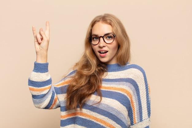 幸せ、楽しさ、自信、前向きで反抗的な感じ、手で岩や重金属の看板を作る金髪の女性