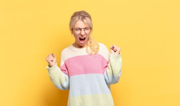 Блондинка чувствует себя счастливой, позитивной и успешной, празднует победу, достижения или удачу