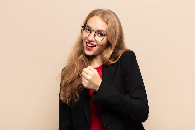 도전에 직면하거나 좋은 결과를 축하 할 때 행복하고, 긍정적이고, 성공하고, 동기 부여 된 금발의 여자