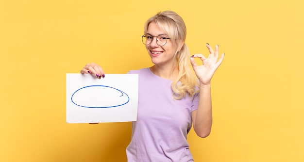 Blonde woman feeling happy, relaxed and satisfied, showing approval with okay gesture, smiling
