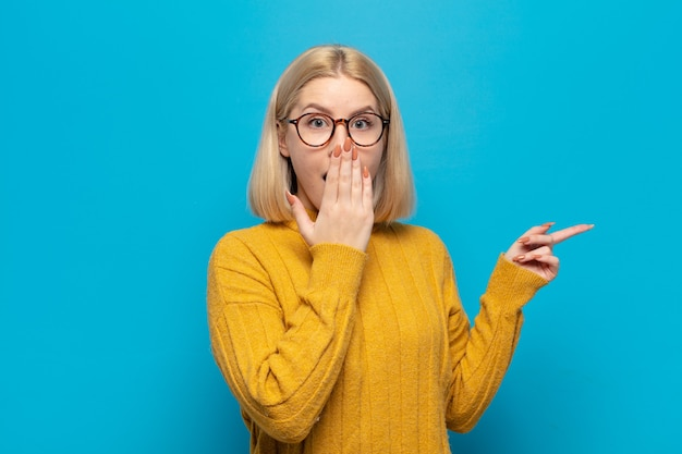 Blonde woman feeling happy, shocked and surprised, covering mouth with hand and pointing to lateral copy space