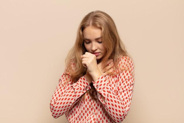 Блондинка чувствует себя плохо с симптомами гриппа и болью в горле, кашляет с прикрытым ртом